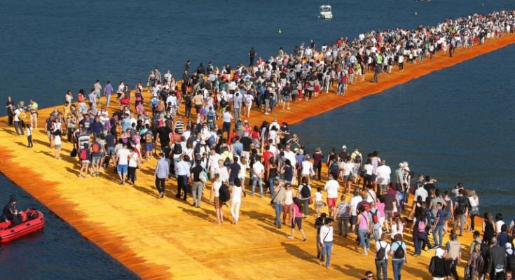 epa05375852 People walk the 'The Floating Piers' by  Bulgarian artists Christo and Jeanne-Claude on Lake Iseo during the opening of the art work near Sulzano, northern Italy, 18 June 2016. The 'Floating Piers' with their bright orange covers will be open until 03 July and will connect the two towns Sulzano and Monte Isola.  EPA/FILIPPO VENEZIA