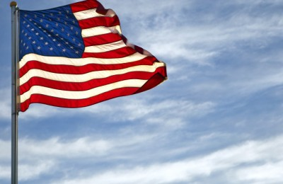 A vivid American Flag flys on a blue sky