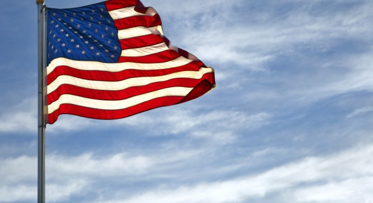 A vivid American Flag flys on a blue sky