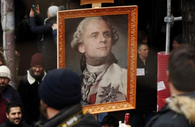 epa08046776 Protesters hold a portrait of French President Emmanuel Macron portrayed as Louis XVI King of France during a demonstration against pension reforms Paris, France, 05 December 2019. Unions representing railway and transport workers and many others in the public sector have called for a general strike and demonstration to protest against French government's reform of the pension system.  EPA/CHRISTOPHE PETIT TESSON