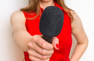 Female reporter with black microphone making interview - journalism and broadcasting concept