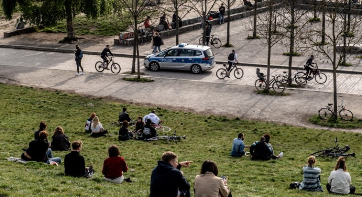 epa08367006 Police car on guard while people enjoy a sunny evening at the Wall Park (lit.: Mauerpark) in Berlin, Germany, 16 April 2020. Countries around the world are taking increased measures to stem the widespread of the SARS-CoV-2 coronavirus which causes the Covid-19 disease.  EPA/FILIP SINGER