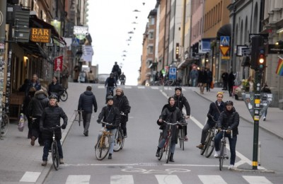 epa08337470 Cyclists wait for the green light on a street in the Sodermalm district of Stockholm, Sweden, 01 April 2020. The streets of the Swedish capital are less crowded than usual due to the ongoing pandemic of the COVID-19 disease caused by the SARS-CoV-2 coronavirus.  EPA/JESSICA GOW / TT SWEDEN OUT