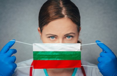 Coronavirus in Bulgaria Female Doctor Portrait hold protect Face surgical medical mask with Bulgaria National Flag. Illness, Virus Covid-19 in Bulgaria, concept photo