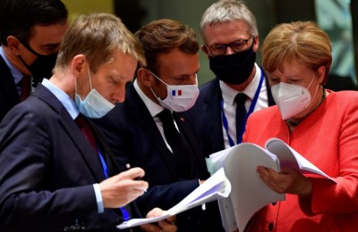 epaselect epa08557305 German Chancellor Angela Merkel (R) chats with French President Emmanuel Macron (C) while both wear face masks during a roundtable discussion on the fourth day of the ongoing Special European Council leaders' summit, the first face-to-face meeting between EU statespeople held since the eruption of the ongoing pandemic of the COVID-19 disease caused by the SARS-CoV-2 coronavirus, in Brussels, Belgium, 20 July 2020. The heads of state and government discussed the bloc's response to the pandemic and the new long-term budget.  EPA/JOHN THYS / POOL